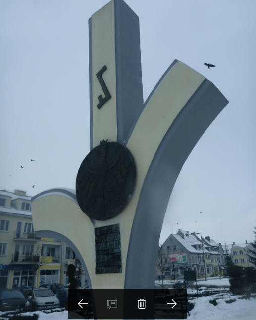 A bird flies past the War Memorial tourist Biskupiec