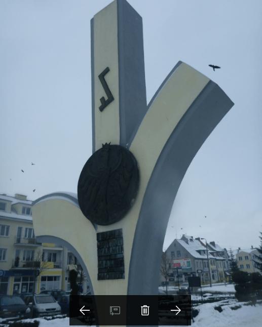 A bird flies past the War Memorial tourist Biskupiec